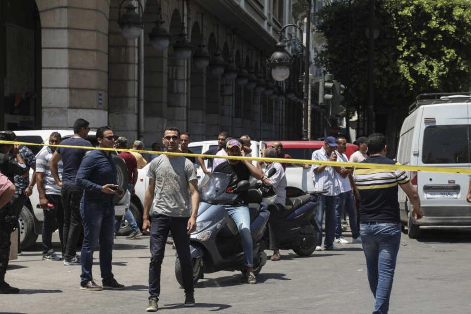 Menschen stehen am 27. Juni hinter einem Absperrband am Tatort.