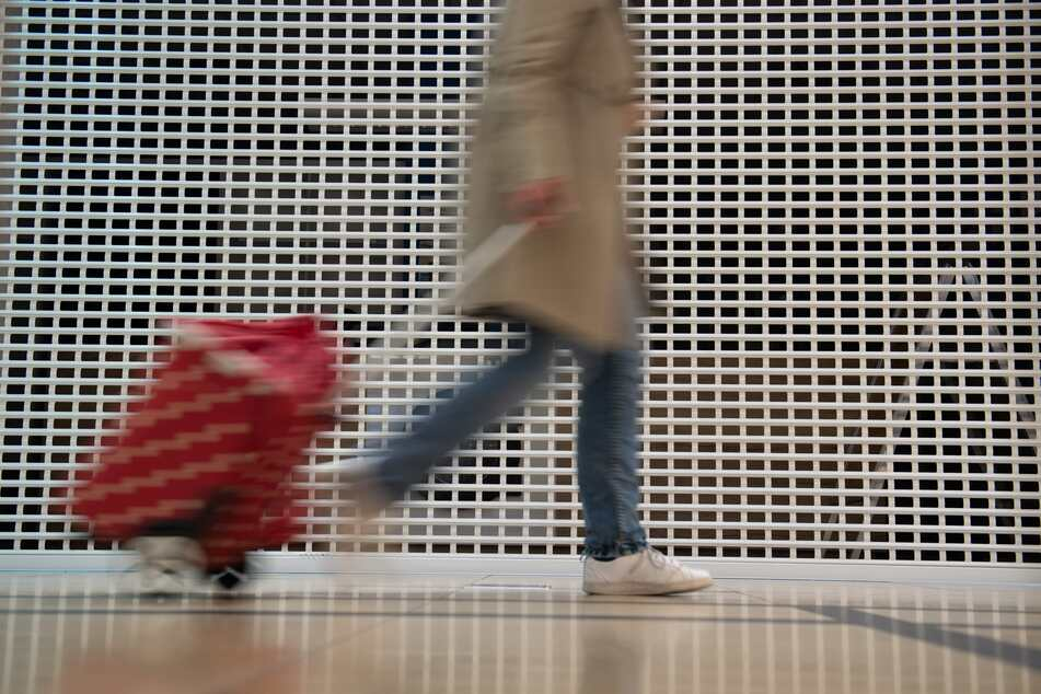 """Eine Frau geht mit einem Trolley bei geschlossenen Geschäften entlang. Zwar können Händler in Sachsen nun """"Click & Collect"""" anbieten. Doch eine richtige Öffnung ersetzt das nicht."""