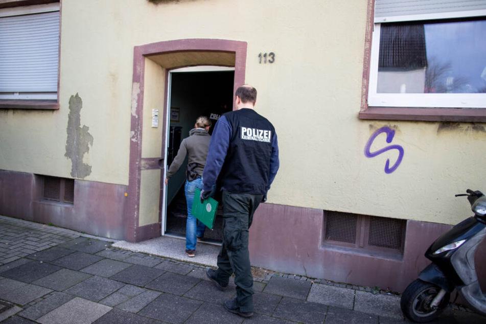Beamte der Spurensicherung gehen in ein Mehrfamilienhaus.