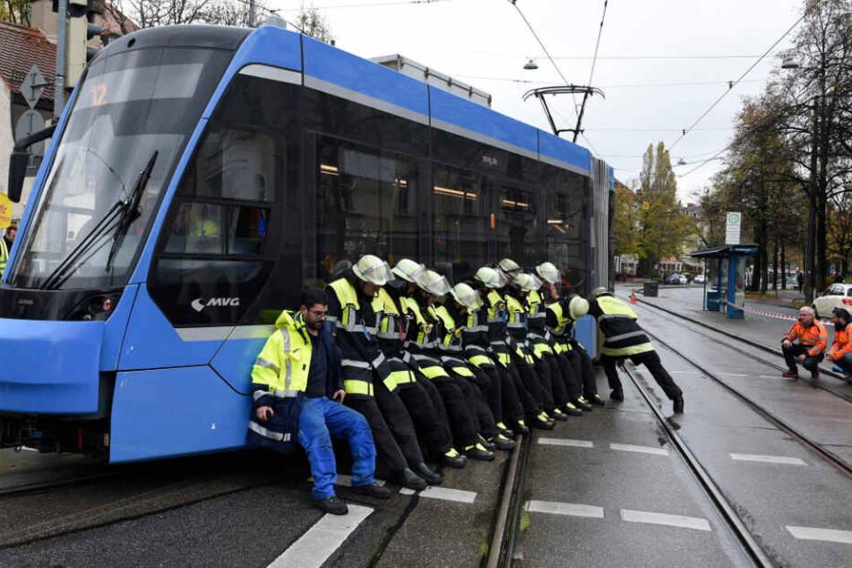 Die Feuerwehrleute stemmen sich gegen die entgleiste Tram, um sie zurückzuschieben.