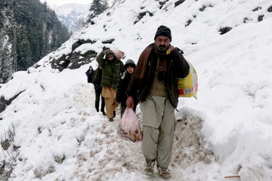 Kaschmirische Dorfbewohner gehen nach starken Schneefällen im Gebiet Neelum in der von Pakistan kontrollierten Region Kaschmir auf einem schneebedeckten Pfad.