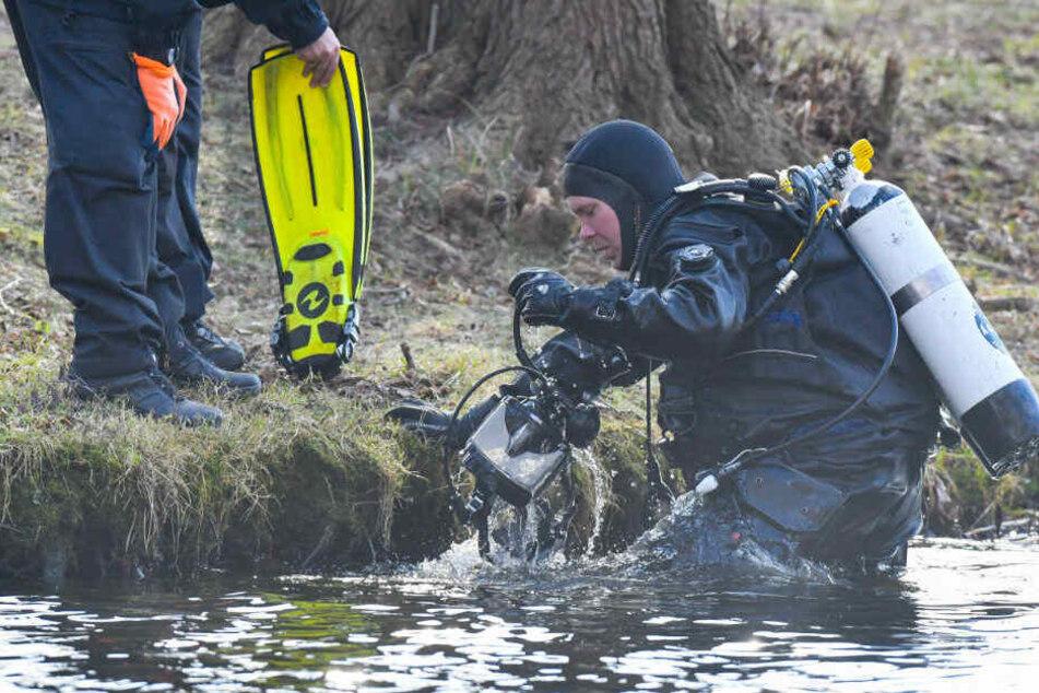 Ein Polizeitaucher kommt aus dem Wasser des Storkower Sees.