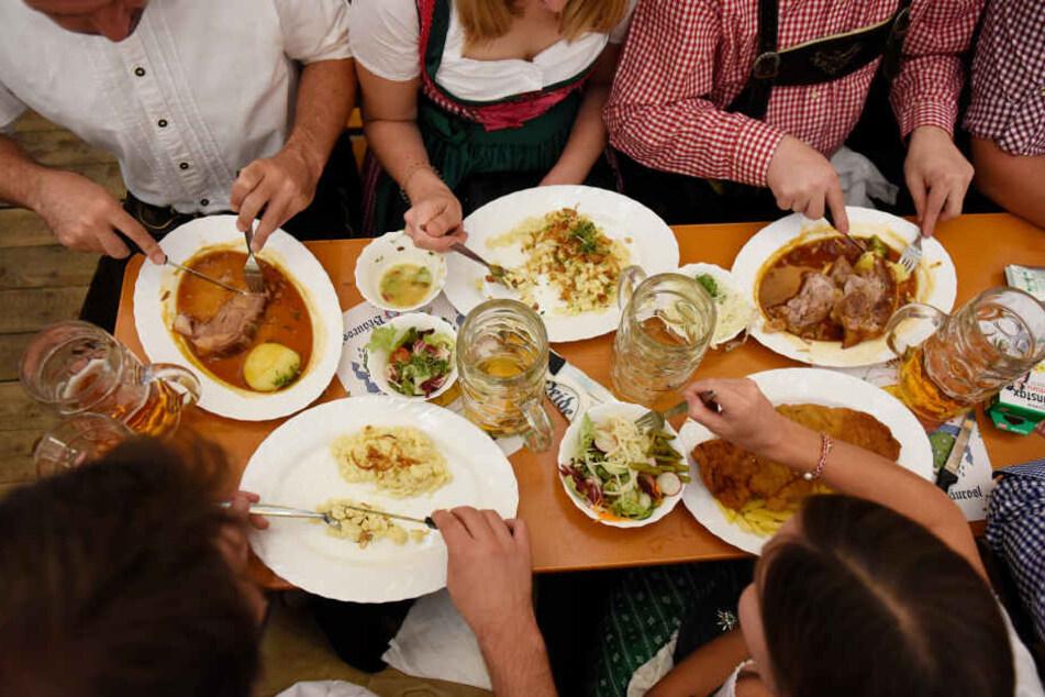Gäste essen in einem Zelt auf dem Oktoberfest: Hier kommt vor allem deftige Wirtshauskost auf den Tisch.
