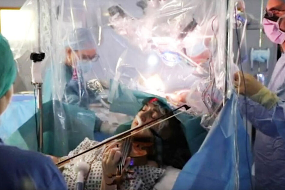 Frau spielt Violine, während Hirn-OP