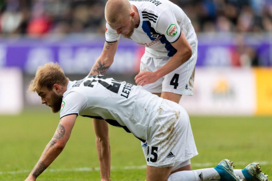 Rick van Drongelen (rechts) kümmert sich um Timo Letschert, der nach einem Zusammenstoß benommen am Boden hockt.
