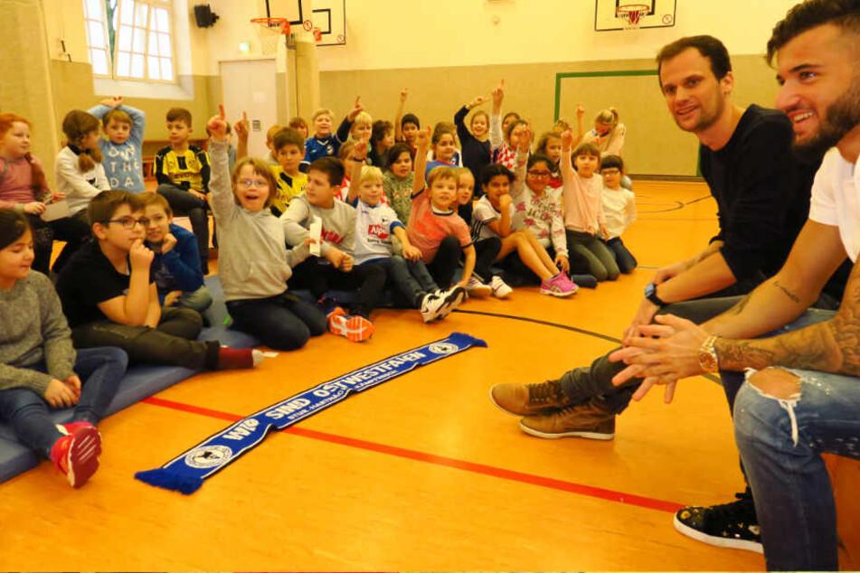 Arminias Keanu Staude (r.) und Sportlehrer Tobias Limberg beantworten die Fragen der Kinder.