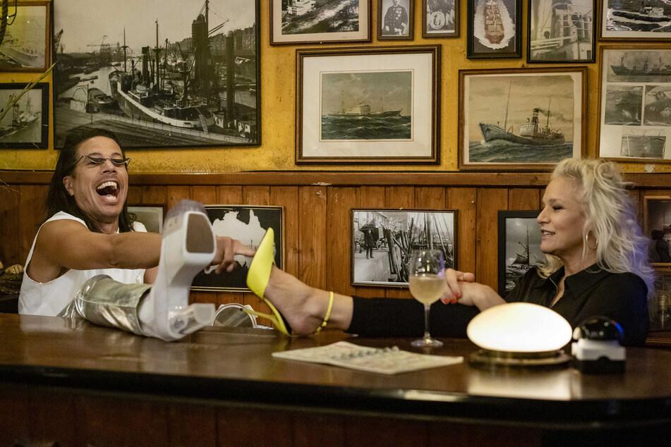Jorge González (53) und Ina Müller (55) beim Schuhvergleich.
