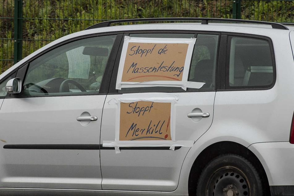 """""""Stoppt die Massentestung"""" und """"Stoppt Merkill!"""" steht auf einem Auto, welches an der Demo teilnahm."""