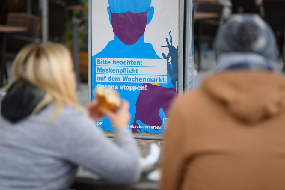 """Ein Paar sitzt auf dem Marktplatz von Offenbach vor einem Plakat mit der Aufschrift """"Bitte beachten: Maskenpflicht auf dem Wochenmarkt. Corona stoppen!""""."""