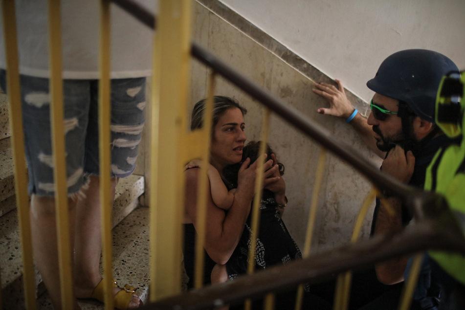 Menschen sitzen auf den Stufen in einem Haus, als die Stadt Ashkelon von Raketen aus dem Gazastreifen beschossen wird. Nach Angaben der Armee ertönten am Dienstagmittag auch in der Hafenstadt Aschdod Warnsirenen. Die Stadt liegt nördlich von Aschkelon an der Mittelmeerküste.