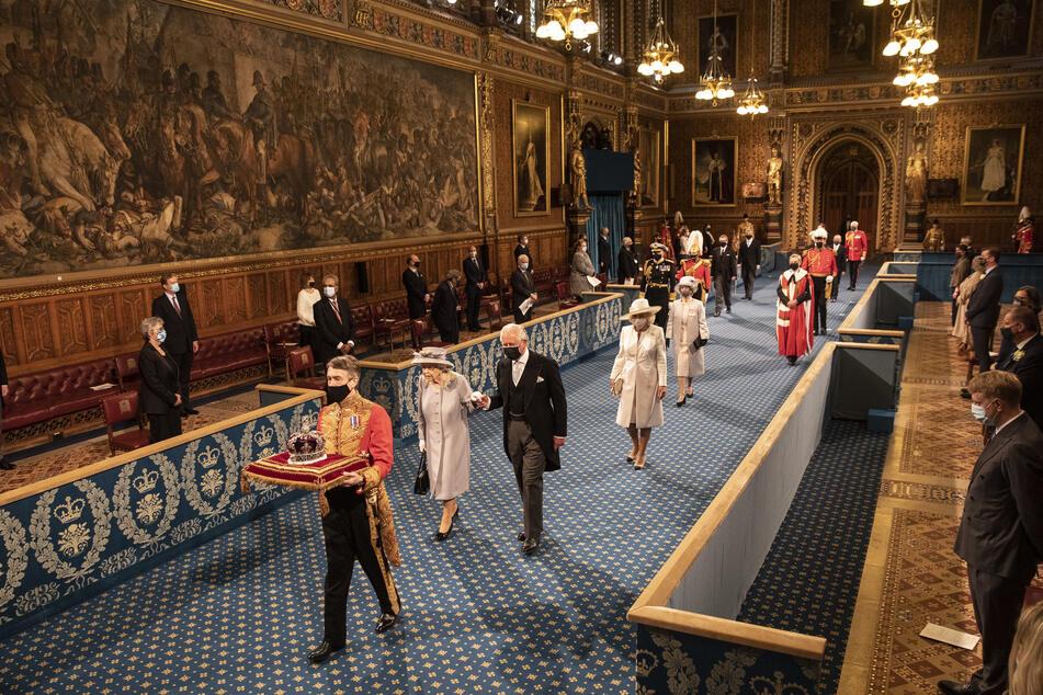 Die Queen schreitet vor ihrer Rede mit ihrem Sohn, Prinz Charles (72), durch die Royal Gallery.