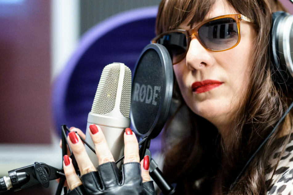 Dea Levina, Mental Domina, haucht in einem Tonstudio in ein Mikrophon.