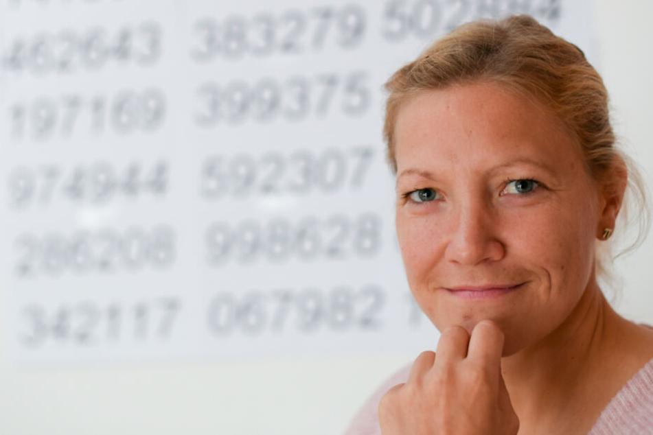 Pi-Gedächtnissportlerin Susanne Hippauf sitzt in ihrer Wohnung vor Zahlenreihen.
