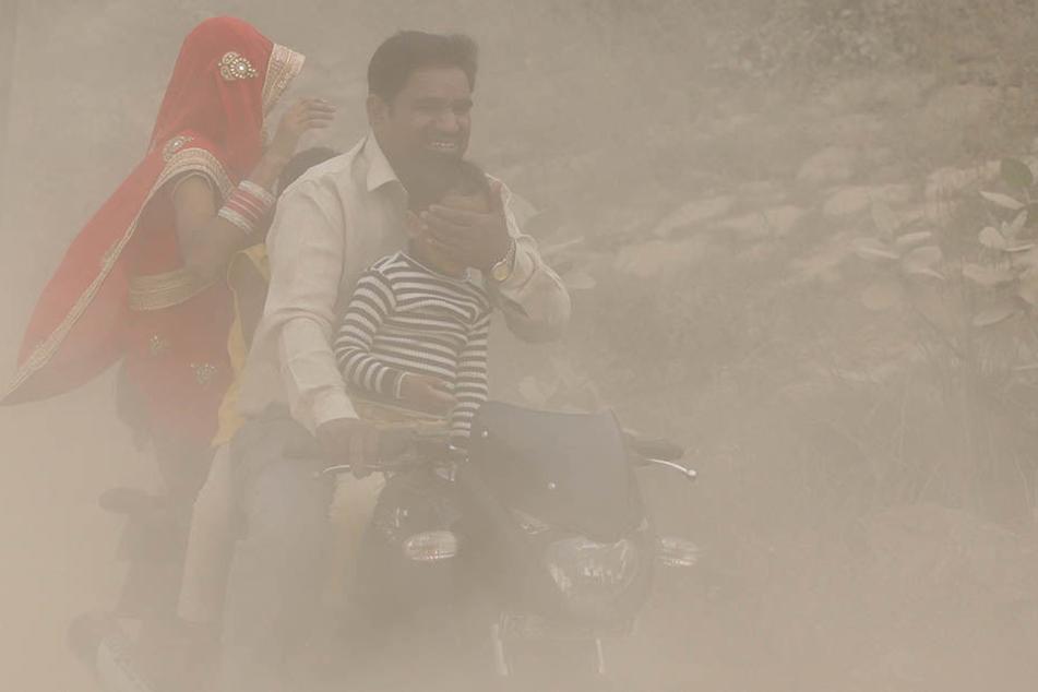 Ein Mann fährt in Neu Delhi seine Familie auf einem Motorroller durch dichten Smog- Nebel und hält seinem Sohn die Augen zu.