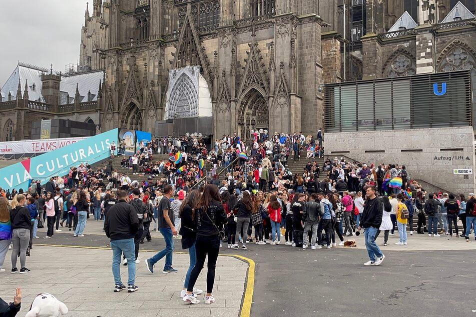 Menschen versammeln sich am Kölner Dom für die CSD-Parade.
