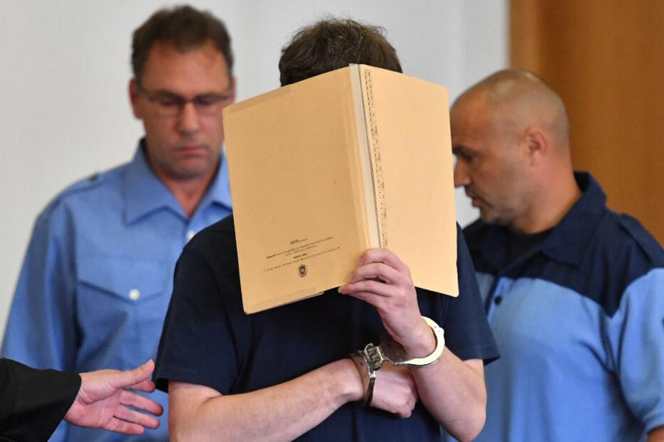 Mit einem Aktenordner vor dem Gesicht, betritt der mutmaßliche Mörder Silvio S. am 26.07.2016 für die Verkündung des Urteiles in Potsdam (Brandenburg) einen Saal des Landgerichtes. (Archivbild)