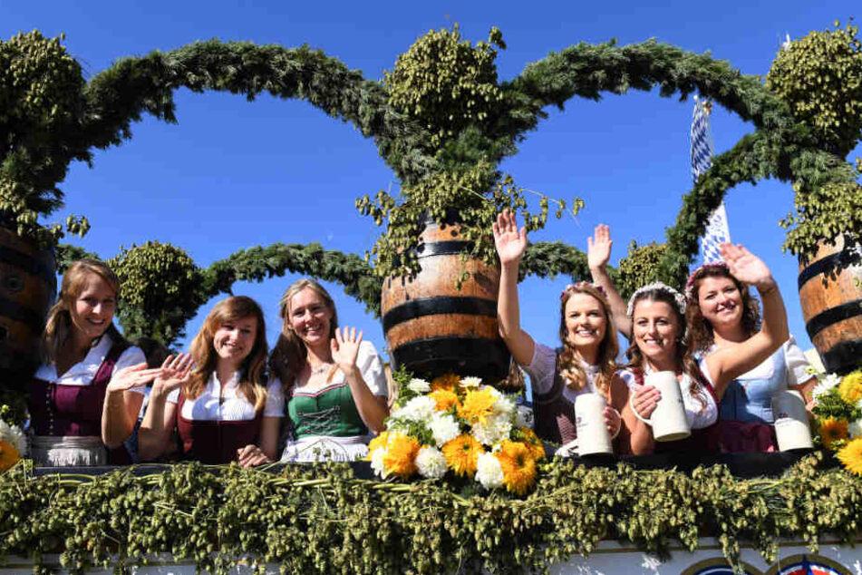 Auftakt zum Oktoberfest. Bedienungen winken beim Einzug der Festwirte auf einem geschmückten Wagen.