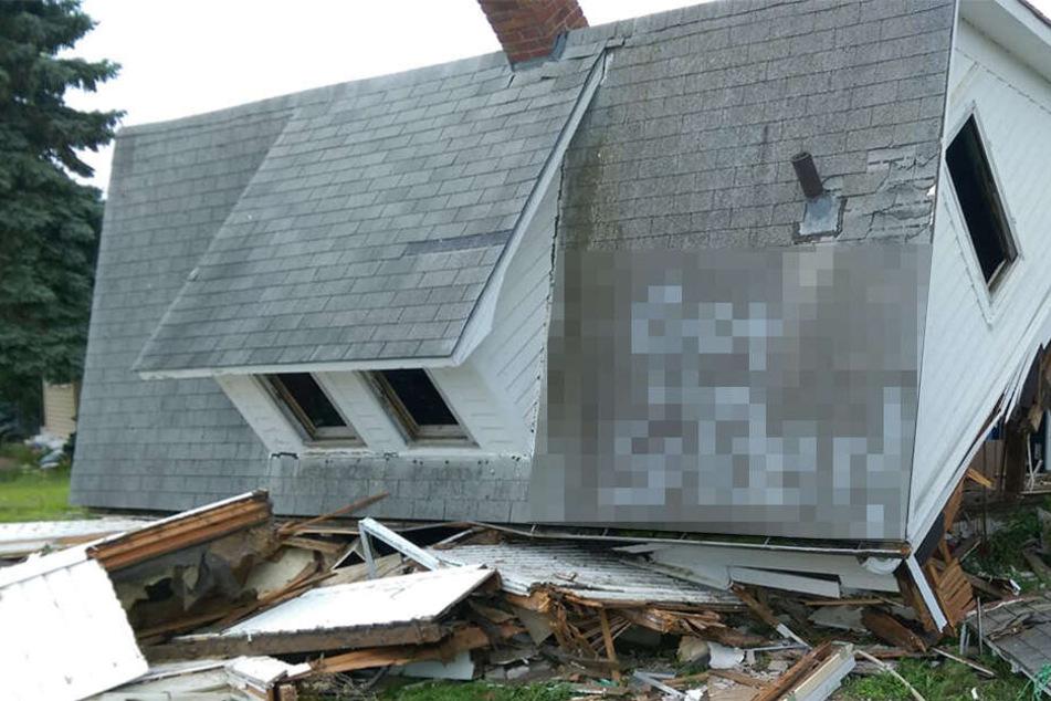 Mann kann nicht fassen, was an dieses zerstörte Haus gesprayt wurde und macht sofort ein Foto