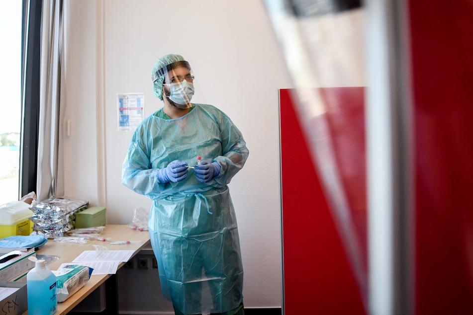 Ein Arzt nimmt in einer Corona-Teststelle einen Abstrich für einen Coronavirus-Test.