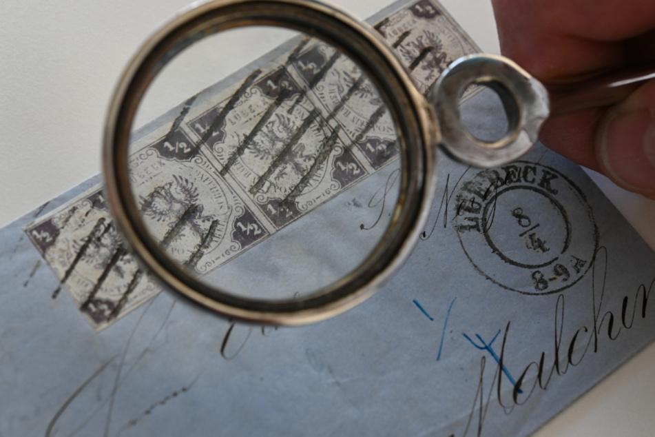 Ein Brief von 1859 ist mit Lübecks ersten Briefmarken, einer Wappenausgabe in dunkellila mit Wasserzeichen, im Wert von je einem halben Schilling frankiert wird mit einer Lupe betrachtet.