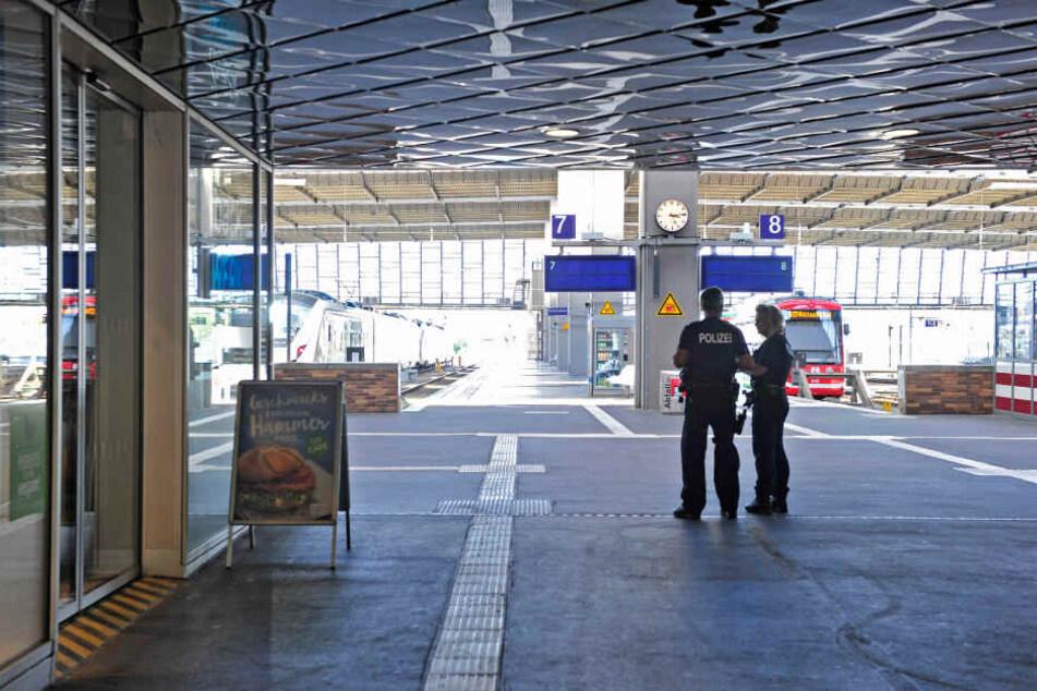 Polizisten stehen in dem menschenleeren Bahnhof.