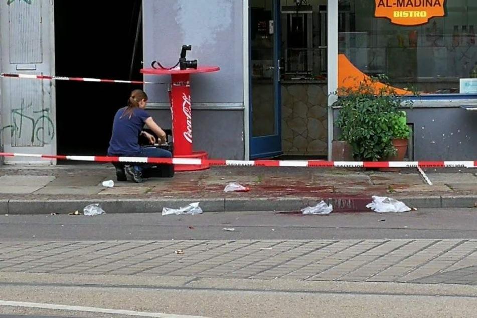 Eine Beamtin der Spurensicherung dokumentiert am Tatort die Lage der Blutspuren.