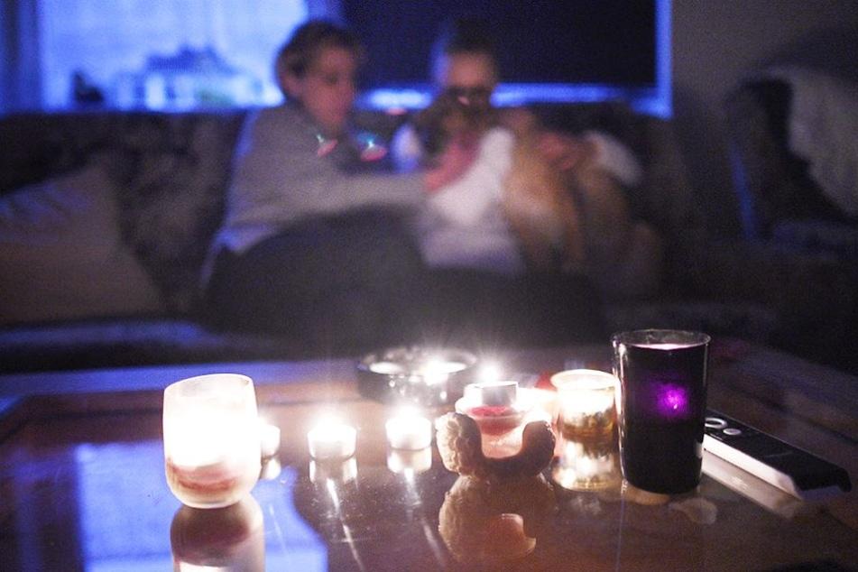 Strom abgedreht: Eine Mutter sitzt mit ihrem Sohn in einer mit Kerzen beleuchteten Zimmer.