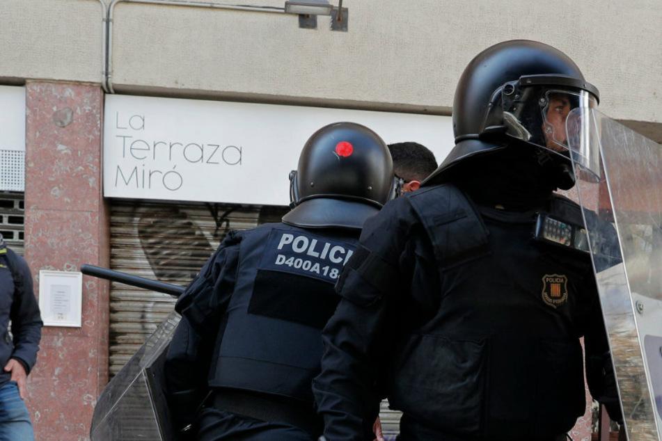 Spanische Polizeibeamte stehen in Barcelona auf der Straße (Symbolbild).