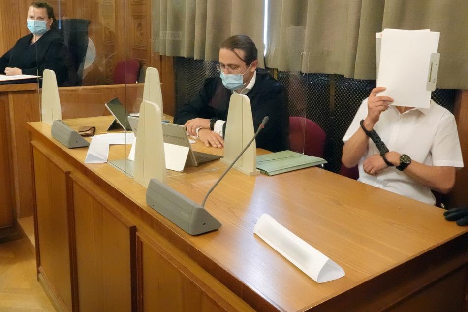 Tübingen, 22. Juli: Im Prozess am Landgericht Tübingen um ein illegales Waffenlager verdeckt der Hauptangeklagte (r.) neben seinem Anwalt sein Gesicht.