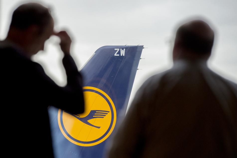 Zwei Männer blicken auf dem Frankfurter Flughafen durch ein Fenster auf eine abgestellte Lufthansa-Maschine.