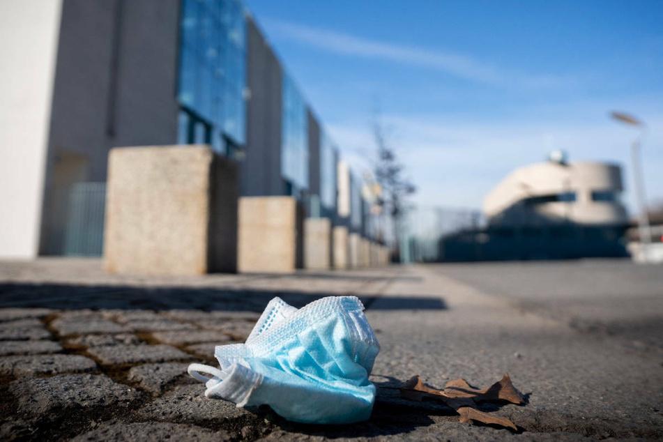 Eine benutzte medizinische Maske liegt vor der Einfahrt zum Bundeskanzleramt. Das Coronavirus breitet sich in Berlin mit unveränderter Geschwindigkeit aus. Am Samstag meldeten die Gesundheitsämter der Stadt 313 neue Infektionen, das waren zwei mehr als am Samstag vergangener Woche.