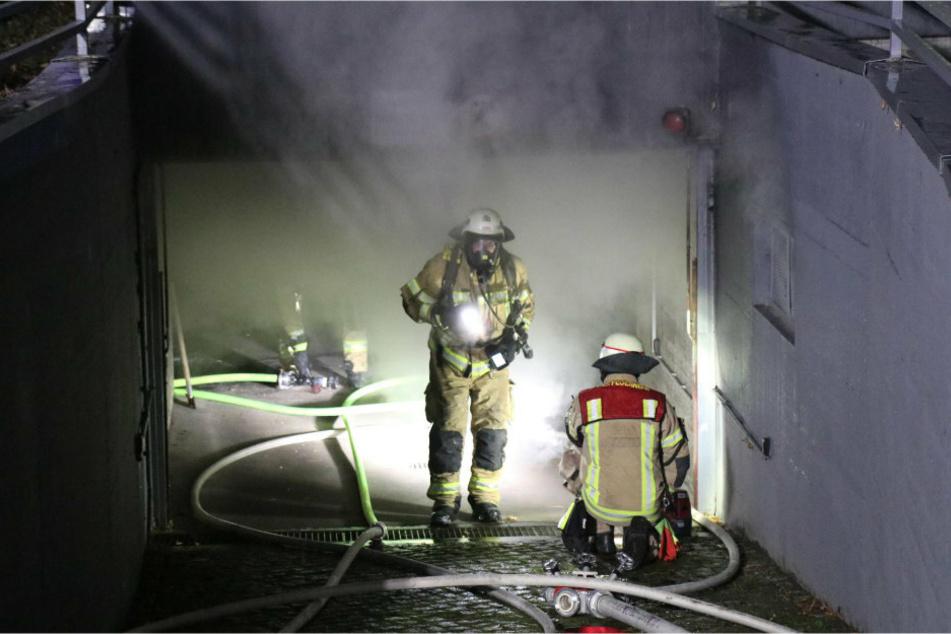 Zwei Feuerwehrleute sind mit Löscharbeiten in der Tiefgarage beschäftigt.