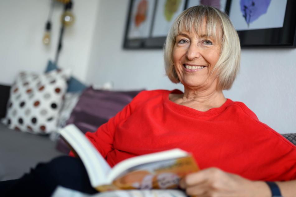Monika Wehn liest ein Buch in ihrer Wohnung.