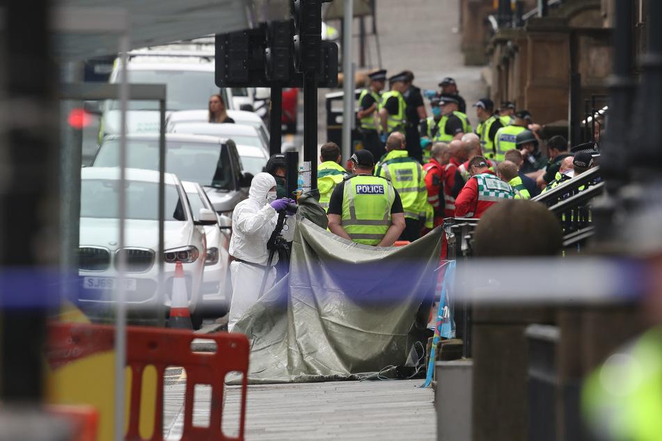 Polizeibeamte und Gerichtsmediziner stehen an einem abgesperrten Tatort in der West George Street.