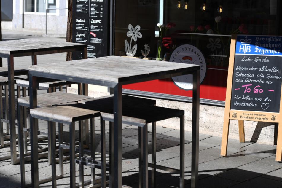 """Leere Tische sind neben einem Schild eines Bistros zu sehen, in dem es nur noch """"To Go"""" Speisen gibt. Die Gastronomie hat an der Corona-Krise zu knabbern."""