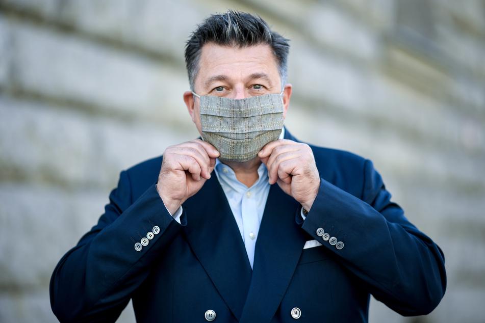 Andreas Geisel (SPD), Senator für Inneres und Sport in Berlin, setzt einen Mund-Nasen-Schutz auf.