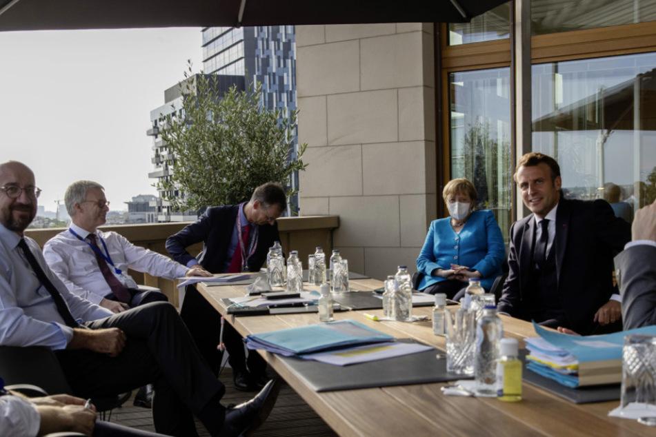 Charles Michel (44, l), Präsident des Europäischen Rates, spricht mit Bundeskanzlerin Angela Merkel (66, CDU, 3.v.r) und Emmanuel Macron (42, 2.v.r), Präsident von Frankreich, auf einer Terrasse des Gebäudes des Europäischen Rats am Rande des zweiten Tags des EU-Sondergipfels.
