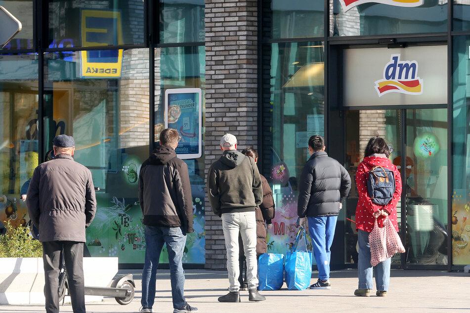 Kunden warten vor einem Drogeriemarkt in Essen.