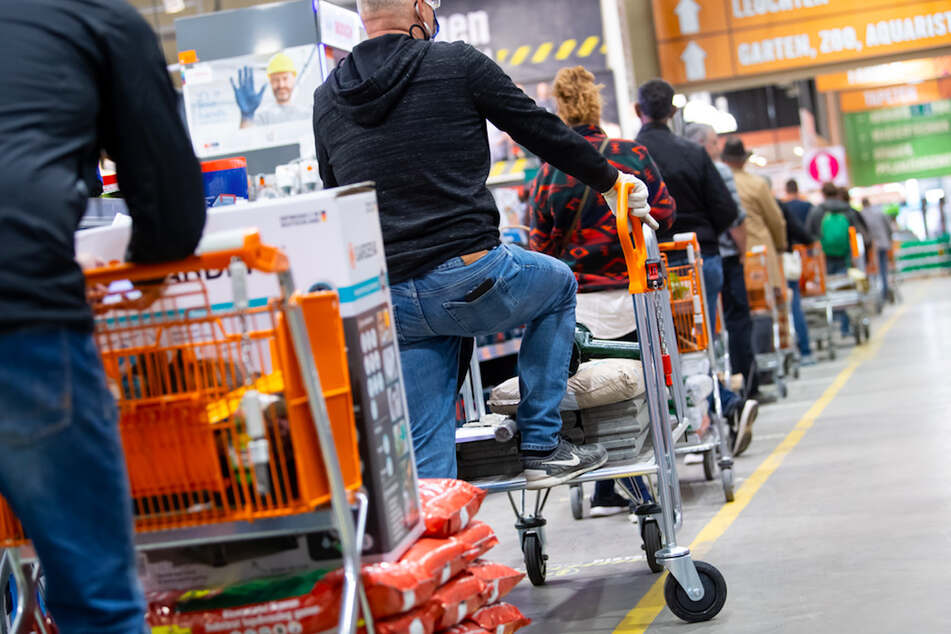 Kunden stehen im Frühjahr 2020 mit Einkaufswagen in einem Hornbach-Baumarkt in einer Schlange vor den Kassen an.
