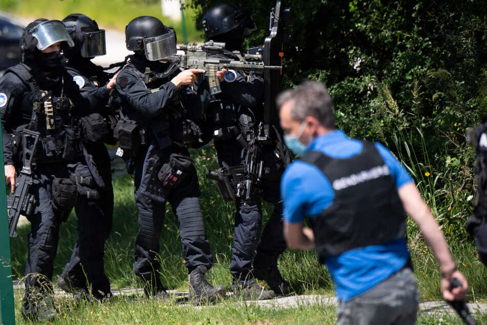 Schwerbewaffnete Polizisten verfolgen den Verdächtigen.