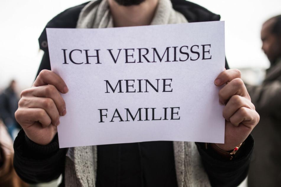 Ein Mitglied des Flüchtlingsrats hält bei einer Kundgebung des Flüchtlingsrats Berlin ein Schild in den Händen.