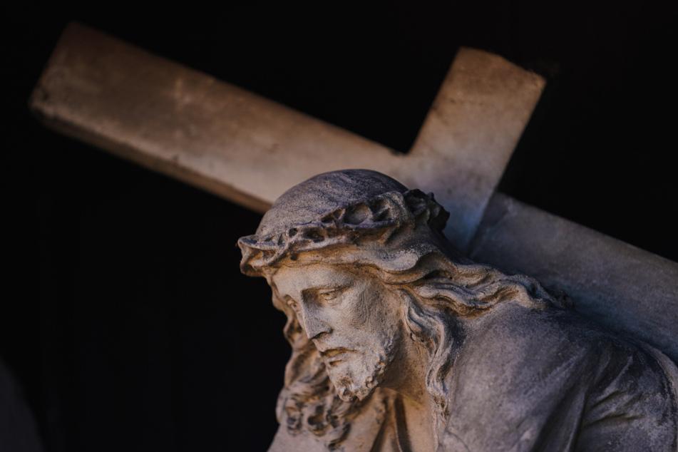 Eine Figur des Jesus Christus mit dem Kreuz ist an einer Fassade in der Bamberger Altstadt zu sehen. Die Kirchen bereiten sich auf Ostern in der Corona-Pandemie vor.