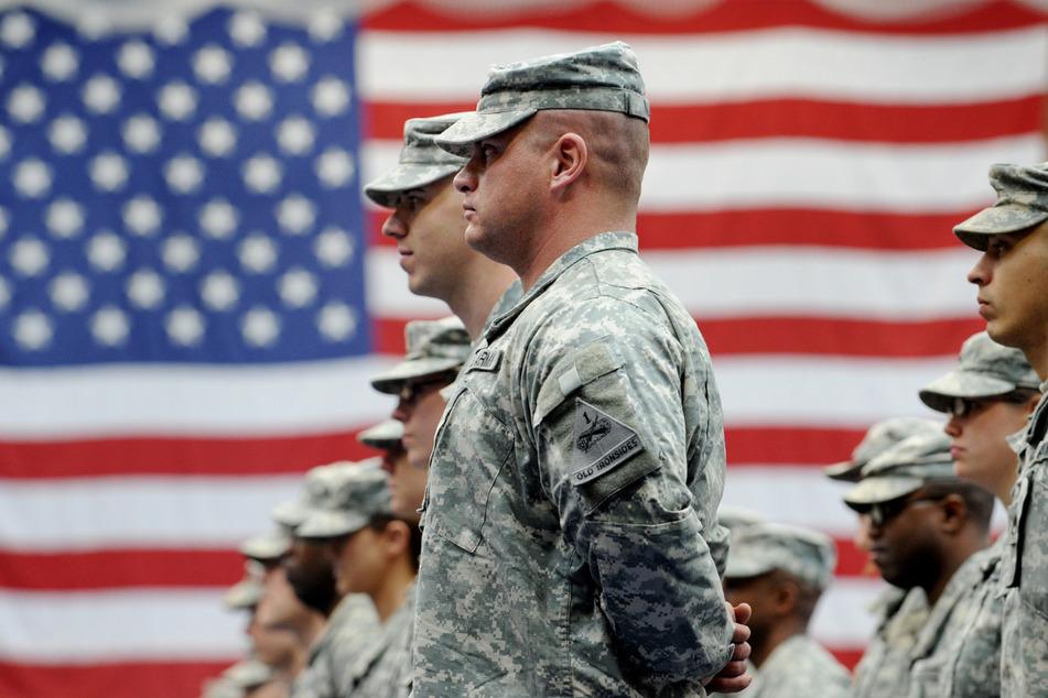US-Soldaten stehen nach ihrer Ankunft auf der US-Airbase in Wiesbaden-Erbenheim vor einer US-Flagge. Die Zahl der US-Soldaten in Deutschland soll um fast 12.000 verringert werden.