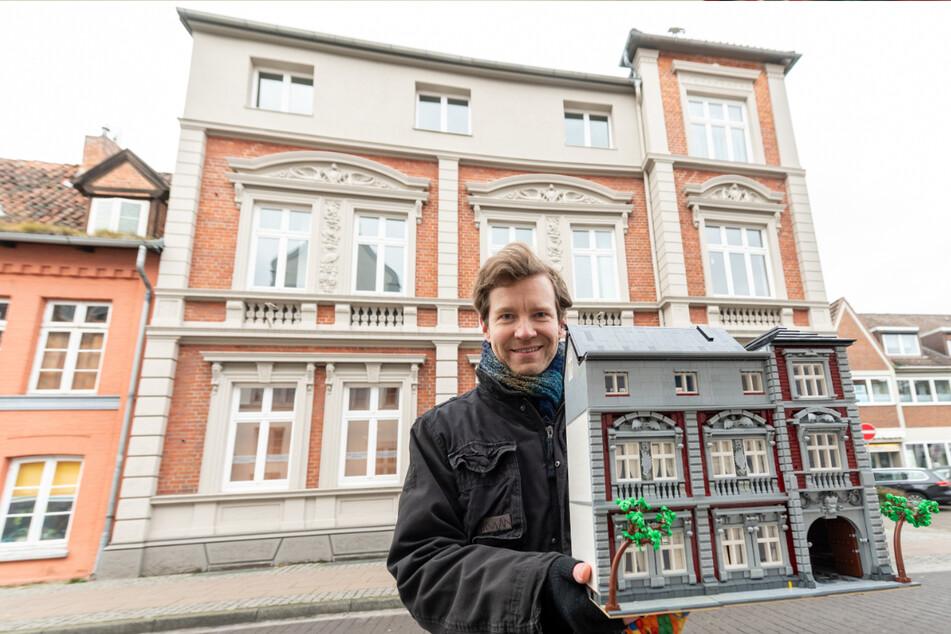 Benjamin Albrecht steht vor einem Lüneburger Gebäude mit einem Nachbau aus Legosteinen.