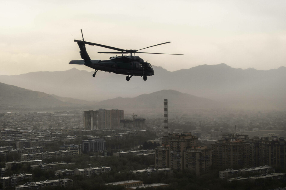 A US Army Black Hawk flies over the city of Kabul.
