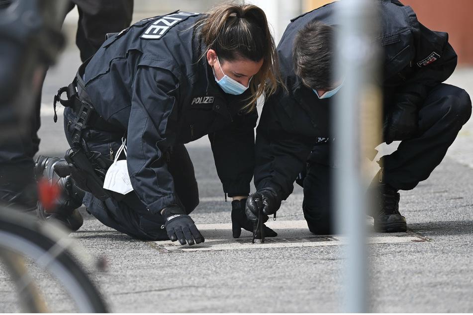 Polizisten suchen auf dem Fußweg und neben den Gebäuden des diakonischen Anbieters Oberlinhaus nach Spuren.