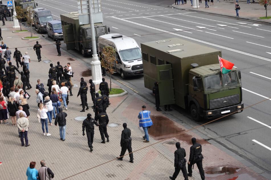Bereitschaftspolizisten stehen vor dem Gefangenentransporter.