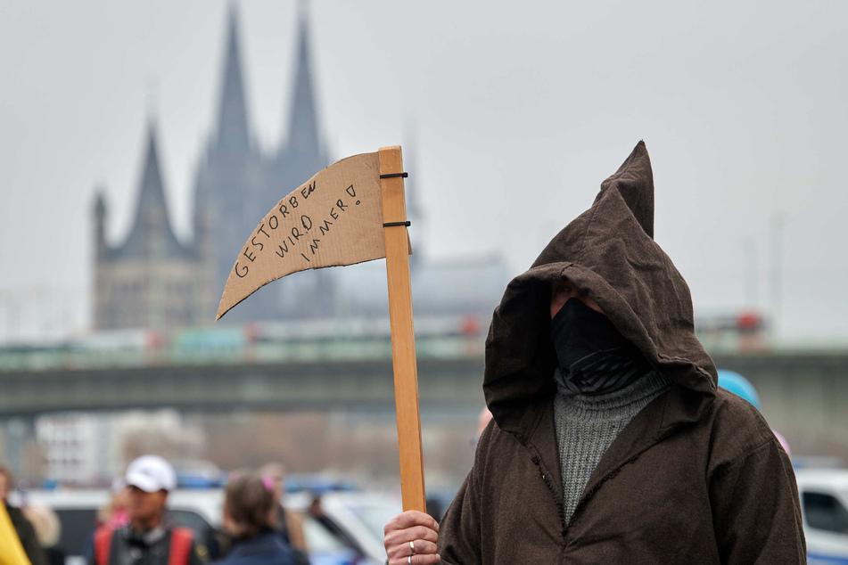 """Ein als Sensenmann verkleideter Teilnehmer einer Demonstration gegen Corona-Schutzmaßnahmen in Köln trägt ein Sense aus Pappe mit der Aufschrift """"gestorben wird immer""""."""