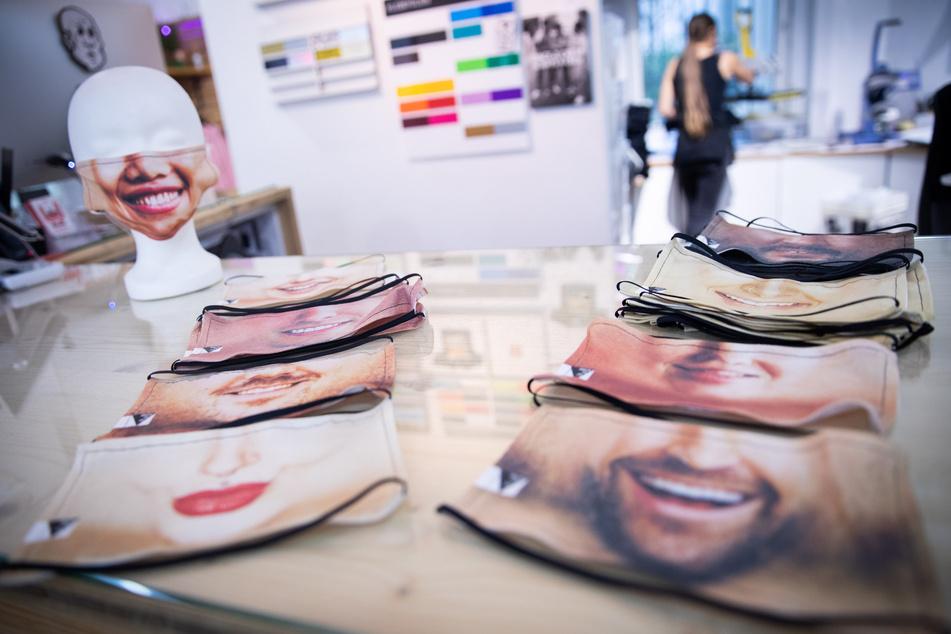 Fotomasken als Mund-Nasen-Schutz liegen in der kleinen Textildruckerei in Hamburg-Winterhude auf einem Tisch.