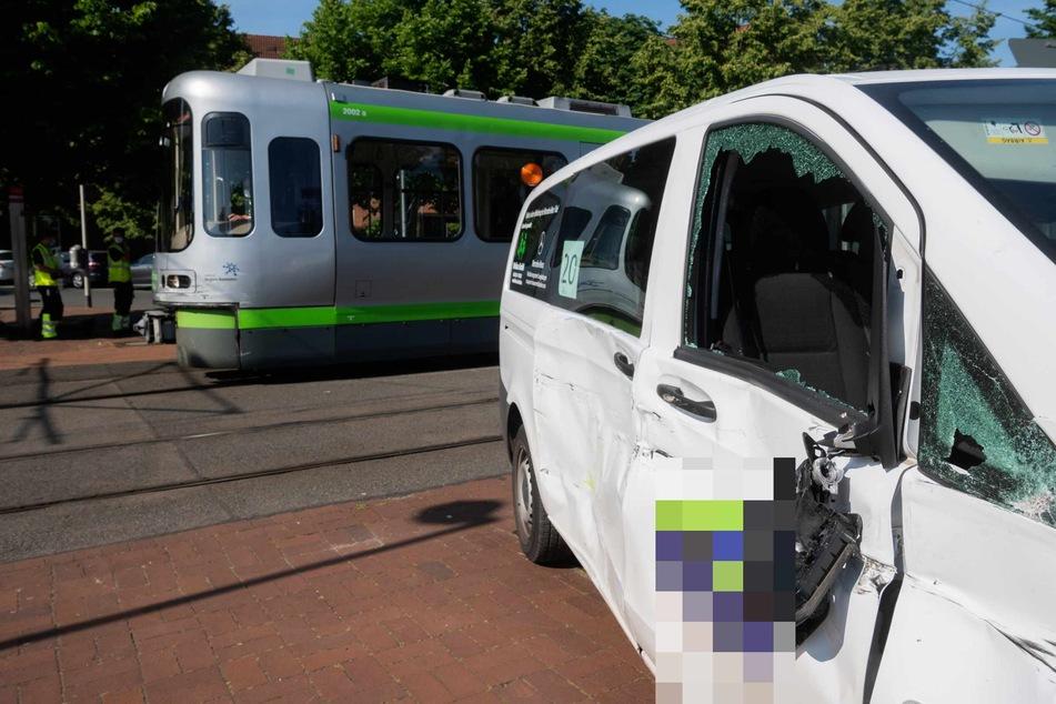 Ein kleiner Schulbus und eine Stadtbahn der Hannoverschen Verkehrsbetriebe uestra stehen nach einem Unfall an einem Bahnübergang.